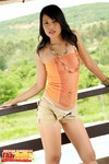 Jupjang Bunrugsa Leaning Against Railing Wearing Orange Top And Tan Shorts