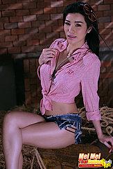 Sitting On Bench Wearing Pink Shirt In Denim Shorts Legs Crossed