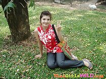 Seated on grass under tree flashing vee sign