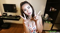 Flashing vee signs wearing flowered top pushing her breasts together