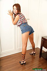 Bending Over Againt Wardrobe Looking Over Her Shoulder Wearing Check Shirt In Denim Shorts High Heels