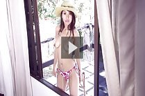 Aor Chan topless in sun hat and bikini bottoms listens to music
